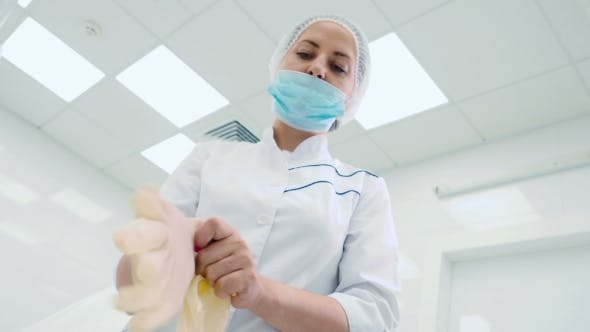 Cover Image for Beautician Put on Hands Latex Gloves in Clinic