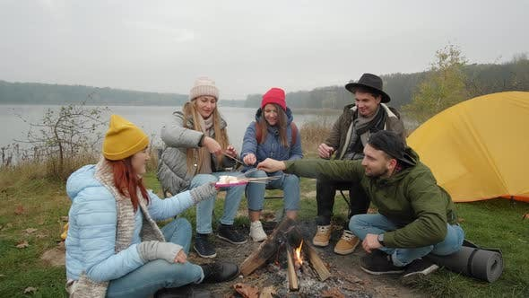 Thumbnail for Group of Happy Friends Around Burning Camping Bonfire in Woods Roasting Marshmallows Talking