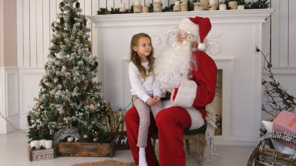 Thumbnail for Cute Little Girl Singing a Christmas Song Sitting on Santa Claus Lap