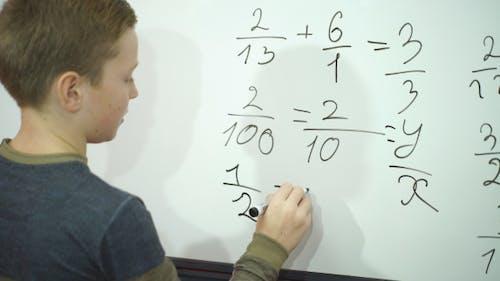 Écolier écrivant quelque chose sur tableau blanc vierge