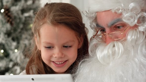 Thumbnail for Happy Girl and Santa Claus Looking at Presents on Tablet PC Next To the Christmas Tree