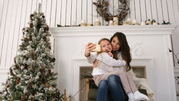 Thumbnail for Cheerful Young Mother and Her Daughter Making Comic Xmas Selfies and Showing Tongues