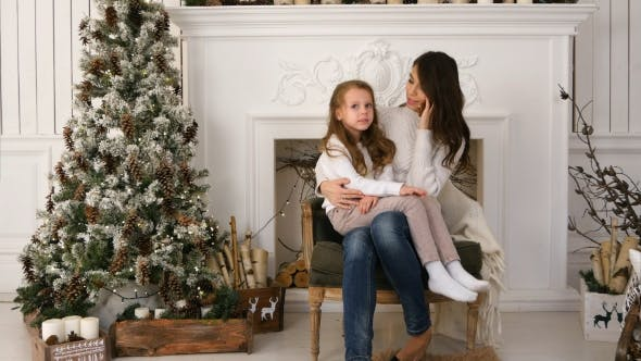 Thumbnail for Young Mother Talking on the Phone with Slightly Bored Daughter Sitting on Her Lap Next To the Xmas