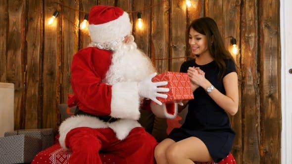 Thumbnail for Santa Claus Giving a Nicely Wrapped Present To a Beautiful Young Woman in Black Dress