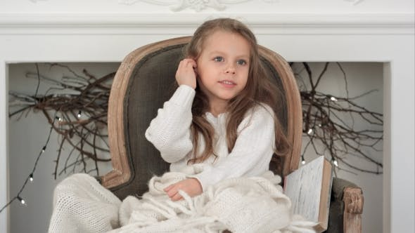 Thumbnail for Little Smiling Girl in White Sweater Sitting on a Chair Wrapped in White Christmas Blanket
