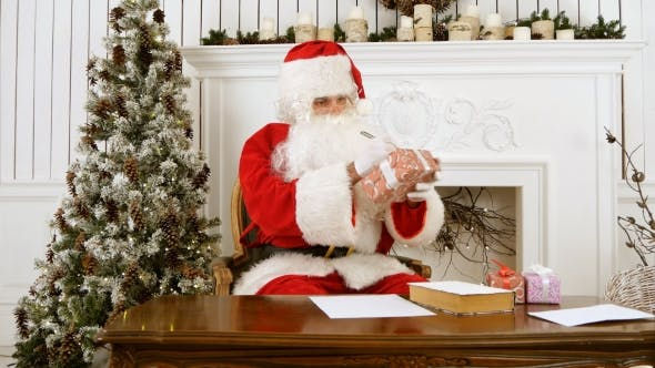 Thumbnail for Santa Claus Sitting at the Table in His Christmas Workshop Signing Presents for Children