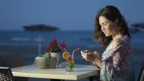 Thumbnail for Beautiful Young Lady Using Mobile Phone at Outdoor Restaurant, Looking to Camera
