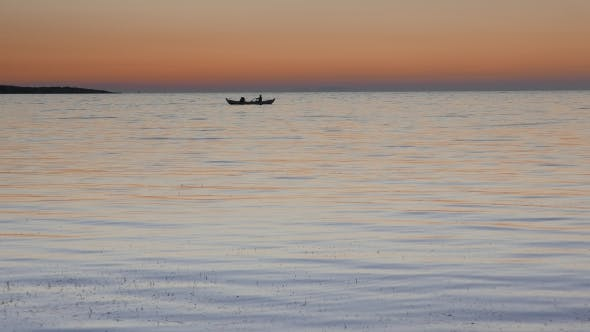 Thumbnail for Calm Sea with a Rowing Boat with Two Fishermen at Sunset.