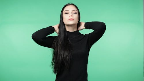 Beautiful Young Brunette Woman in a Black Shirt Playing with the Hair