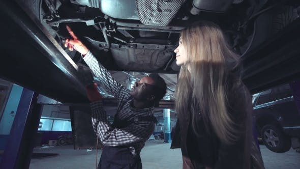 Mechanic Showing Bottom of Car to Woman