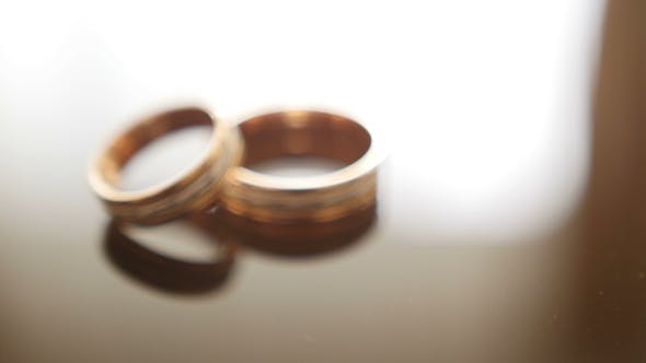 Thumbnail for Golden Wedding Rings on Mirror Glasses Table - One Lies Top of Another