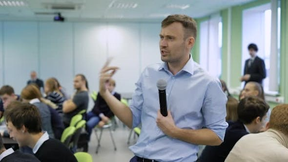 Thumbnail for Professional Coach in Blue Shirt Speaking Into the Microphone and Gesticulating at Workshop for