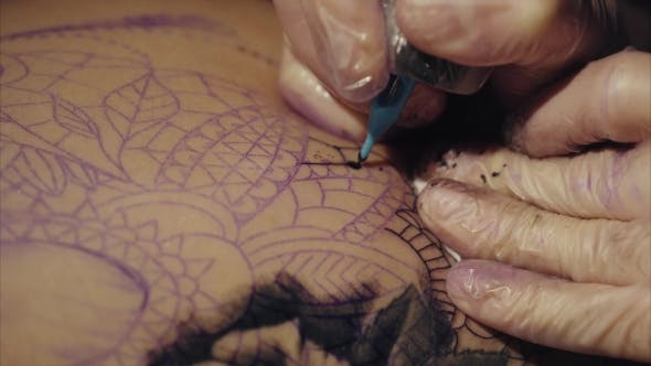 Thumbnail for Hands of Tattoo Artist in Gloves Tattooing a Pattern on Body