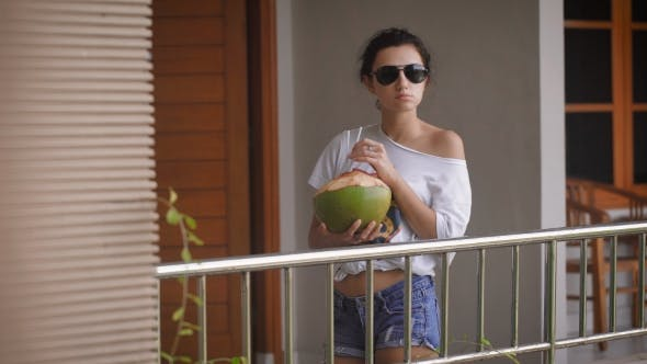 Thumbnail for Young Girl in Sunglasses in the Morning Standing with the Coconut and Drinking Juice