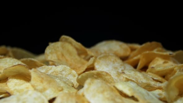 Thumbnail for Potato Chips Rotating On Black Background