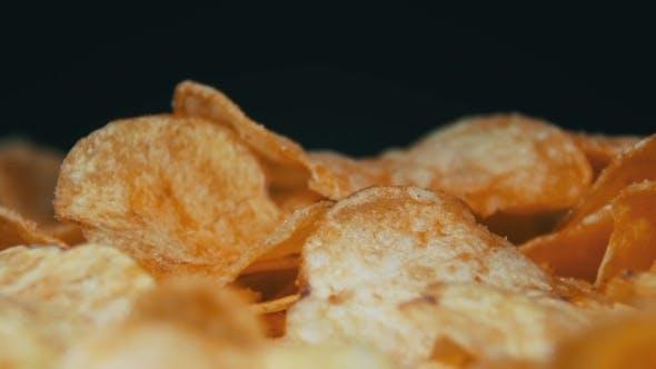 Thumbnail for Kartoffelchips rotierend auf schwarzem Hintergrund