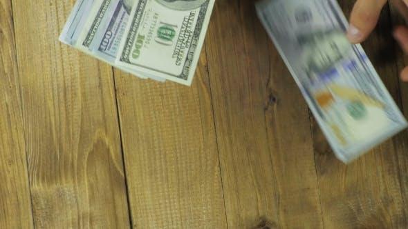 Thumbnail for Dollar Banknoten fallen auf einem Holztisch