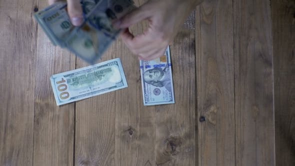 Thumbnail for Dollar Banknotes Falling on a Wooden Table.