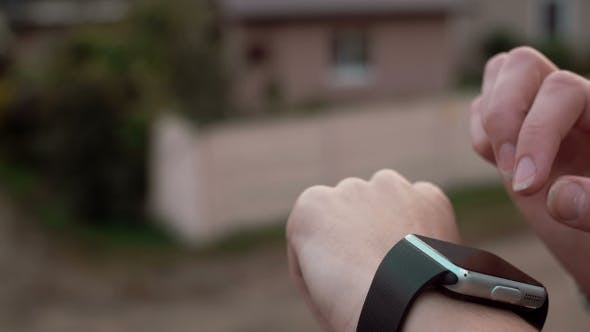 Thumbnail for Woman Using Her Smartwatch Touchscreen Device on a Countryside Background