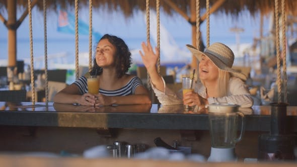 Cover Image for Two Friends at the bar.They Have a Good Mood. Blonde in a Big Straw Hat Showing Something To Her