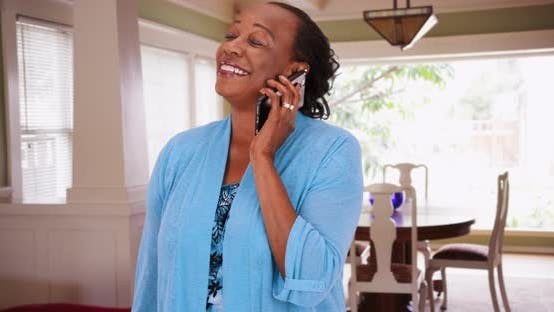 Thumbnail for A black elderly woman uses her smart phone to make a call
