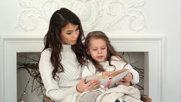 Thumbnail for Young Mother and Her Little Daughter Reading a Christmas Tale Relaxing in an Armchair By the Fire
