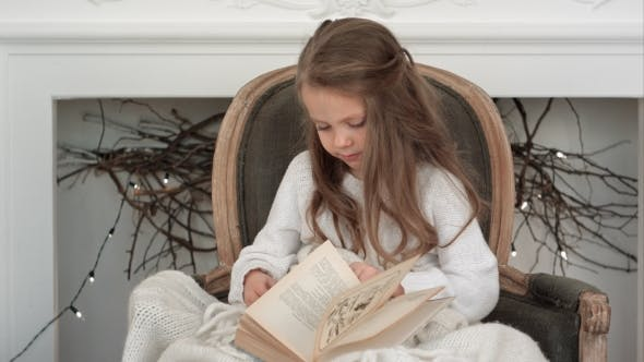 Thumbnail for Cute Little Girl Sitting in a Christmas Chair and Going Through a Book
