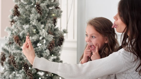Thumbnail for Happy Mother and Daughter Taking Funny Christmas Selfies at Home