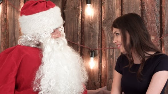 Thumbnail for Pretty Young Woman Telling Santa Her Wishes for Christams and Hugging Him