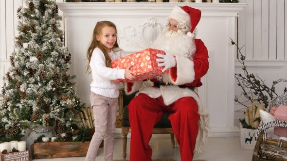 Thumbnail for Santa Claus Giving a Nicely Wrapped Present To a Cute Little Girl