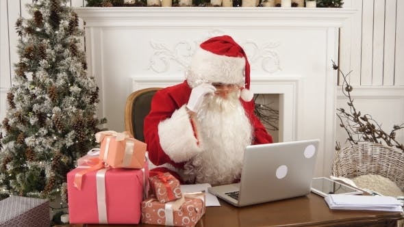 Thumbnail for Modern Santa Claus Working on His Laptop and Preparing Presents