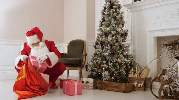 Thumbnail for Santa Claus Putting Presents Back Into His Bag By Christmas Tree
