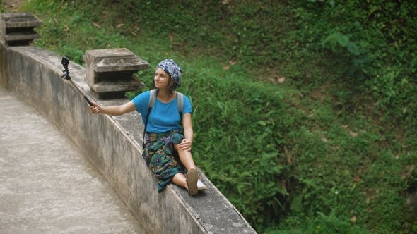 Thumbnail for Smiling Female Traveler Sittting on the Railings of Bridge on Terrace and Holding Selfie-stick