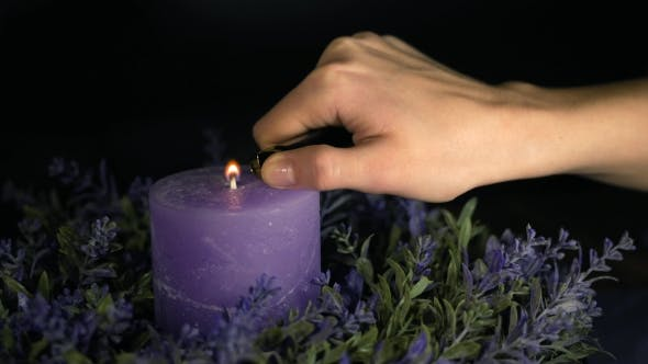Thumbnail for Woman's Hand Lights a Violet Candle with a Lighter and Blows It