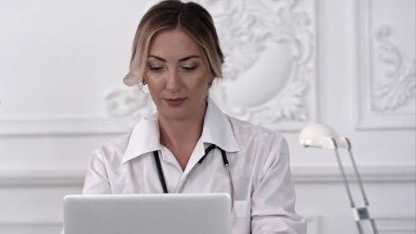 Thumbnail for Female Doctor Sitting on the Desk and Working a Laptop in Hospital