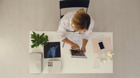 Thumbnail for Female Doctor Using Digital Tablet To Check Patient's Medical Case in Medical Office
