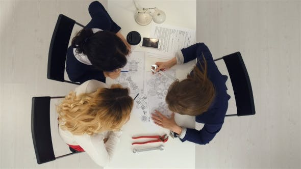Thumbnail for Three Female Engineers Working on Plans at Business Boardroom Table