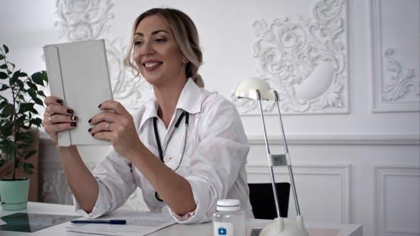 Thumbnail for Female Doctor Making Selfie on Tablet in Office.