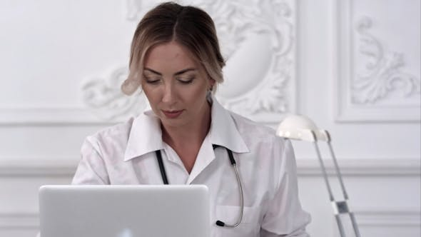 Thumbnail for Serious Female Doctor Using Her Laptop Computer in Medical Office