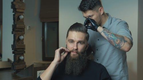 Neue Frisur. Seitenansicht des jungen bärtigen Mannes, der am Friseur mit Haartrockner gepflegt wird, während