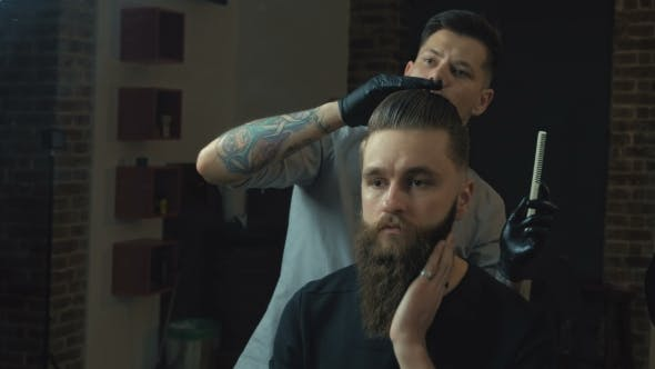 Side View of Young Bearded Man Getting Groomed