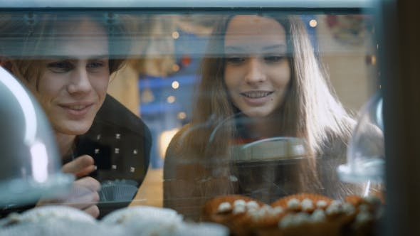 Thumbnail for Beautiful Couple of Young People in a Candy Store. The Girl and the Guy Chosen Cake and Desserts for