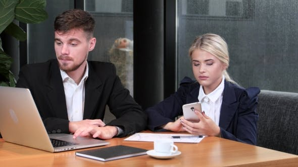 Thumbnail for Two Office Workers Reconcile Their Data Sitting in the Cafe