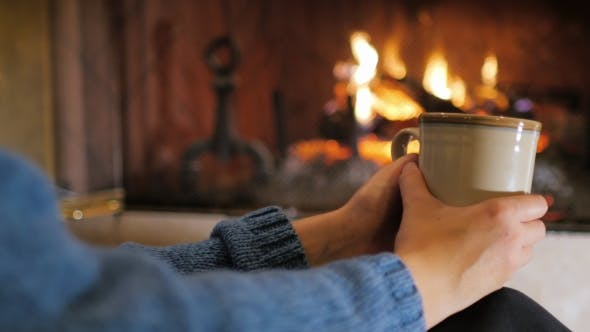 Thumbnail for Hands with a Cup of Tea on a Background of a Burning Fireplace