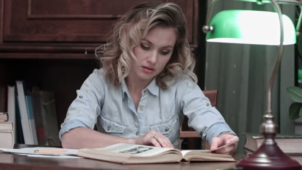Thumbnail for Young Woman Thoughtfully Studying the Book on Her Desk