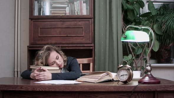 Thumbnail for Tired Female Taking a Nap on Pile of Books at Her Workplace and Being Woken Up By an Alarm