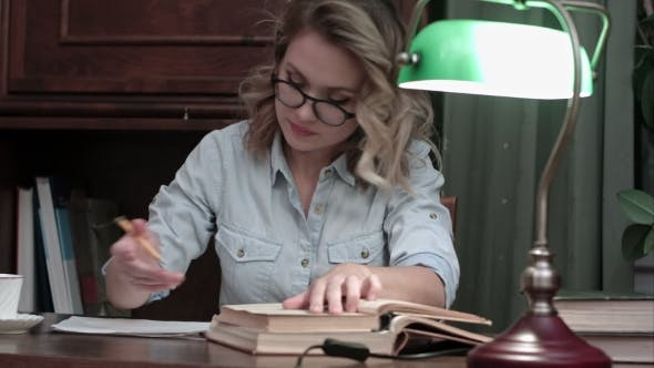 Thumbnail for Busy Student in Glasses Working on Her Report at the Desk with a Green Lamp, Going Through Books and