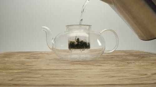 Pouring Boiling Water From Kettle Into White Tea in a Teapot on a Wooden Table