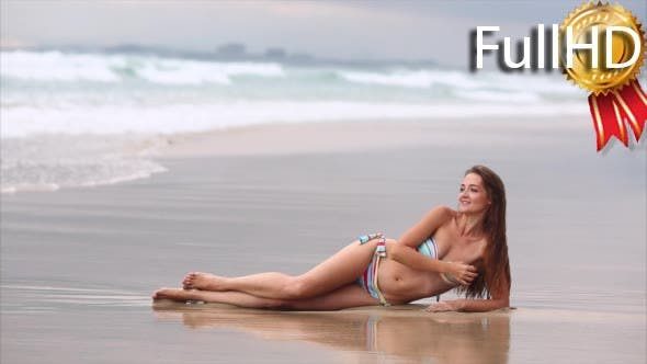 Young Woman in Colorful Swimsuit Lying on the