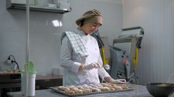 Thumbnail for Joyful Woman Standing Behind a Small Pastry Toque Table on Which Lay a Tray of Eclairs and Carefully